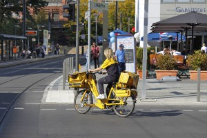 BERLIN, GERMANY - SEPTEMBER 24, 2011: Postwoman moves on her yellow bike on a city street and deliver mail.