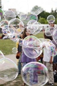 Berlin, Germany - June 10th, 2012: A toung adult woman making giant soap bubbles on an early summer Sunday afternoon at Mauerpark, with the flea market in the background.