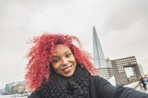 Smiling red hair girl taking selfie in London with Shard skyscraper on background. She is holding the phone and looking at camera. The Shard is a very modern skyscraper, the highest in Europe.