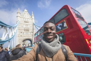 Smiling black man taking selfie in London with Tower Bridge on background. He is holding the phone and looking at camera. Photo taken on a sunny winter day.