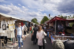 Berlin, Germany - June 10th, 2012: People walking between the various clothing shops at the Mauerpark Sunday flea market on an early summer day