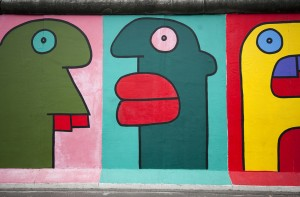 """Berlin, Germany - August 4, 2011: East East Side Gallery is a 1.3km-long section of the wall of Berlin Germany. The paintings are now restored after they suffered badly from vandalism. This graffiti is by artist Thierry Noir."""