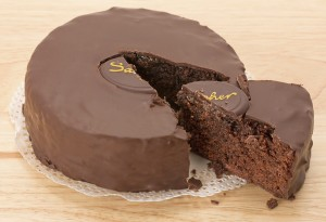 A slice removed from a chocolate Sacher torte cake - studio shot