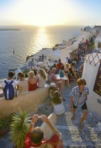 Oia, Santorini, Greece - September 1, 2013: Tourist Crowd watching the sunset in front of the famous old town Oia on Santorini.