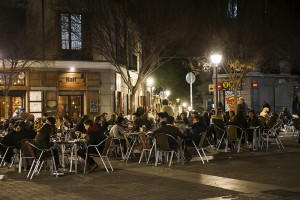 Madrid, Spain - February 21, 2016: Nightlife scene in Madrid streets. People eating and drinking. Tourists and local people sitting in outdoor street cafes. The tourist entertainment district of Madrid with all its retail shops, restaurants, and hotels are a popular destination of many visitors.