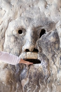 Person sticking their hand in La Bocca della Verit? (English: the Mouth of Truth) in Rome, Italy.