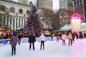 New York, NY, USA - December 10,2013: Ice skaters and tourists near the Christmas tree in Bryant Park on December 10, 2013 in Manhattan.