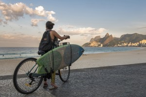 Rio de Janeiro, Brazil - July 7, 2016: Female surfer on a bike looking at the ocean in Ipanema beach.