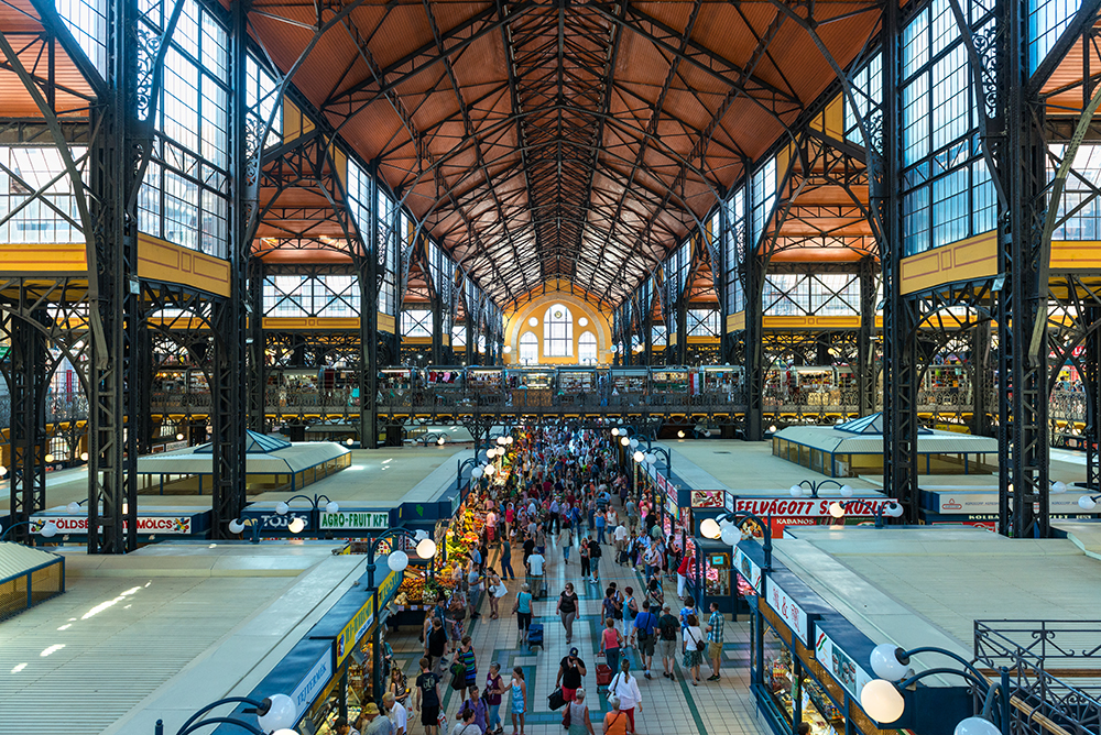 Budapest, Hungary - June 6, 2015: Wide-angle view of the central hall of the Great Market Hall in Budapest, Hungary, full of locals and tourist buying form the different stalls.