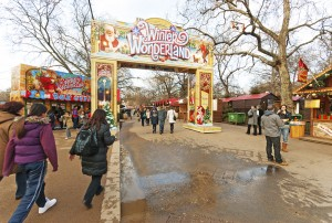 """London, United Kingdom - January 4, 2013: Fairground stall and entrance at the Winter Wonderland event in Hyde Park London, England. Visitors are in the foreground of the image."""