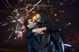 Young couple kissing on New Year's eve. Fireworks in the background.