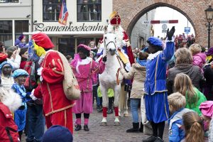Zaltbommel, the Netherlands - November 16, 2013: The arrival of Sinterklaas in the city of Zaltbommel. Sinterklaas and the Zwarte Pieten walking in the streets of Zaltbommel. On the picture Sinterklaas on his horse has just arrived by boat from Spain, together with his helpers called Black Petes. Sinterklaas is a winter holiday figure, it's believed that Sinterklaas brings children presents in the evening of the fifth of December. The arrival of Sinterklaas is always somewhere mid november and also celebrated in many places throughout the country.