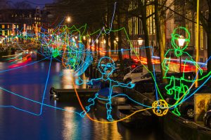 "Amsterdam, The Netherlands - December 17, 2015: Amsterdam canal ""Herengracht"" during the Amsterdam Light Festival with the artwork Paths crossing of Ralf Westerhof, consisting of colorful lines of light in beautiful shapes."