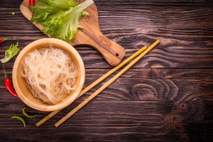 Ingredients of Asian cuisine - rice noodles, leek, lettuce, red hot pepper on a dark wooden background