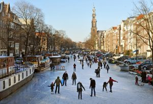 Amsterdam, Netherlands - February, 10th 2012: Skaters on the frozen on the Prinsengracht Canal - a typical Amsterdam scene in winter. The Westerkerk church and moored boats (trapped in the ice) complete the scene