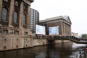 Berlin, Germany - October, 27th 2011: Capture over canal towards museum Pergamon Museum at left side. Outside and on bridge many people are standing in queue for ticketing to museum. Outside at facade are banners for exhibition.