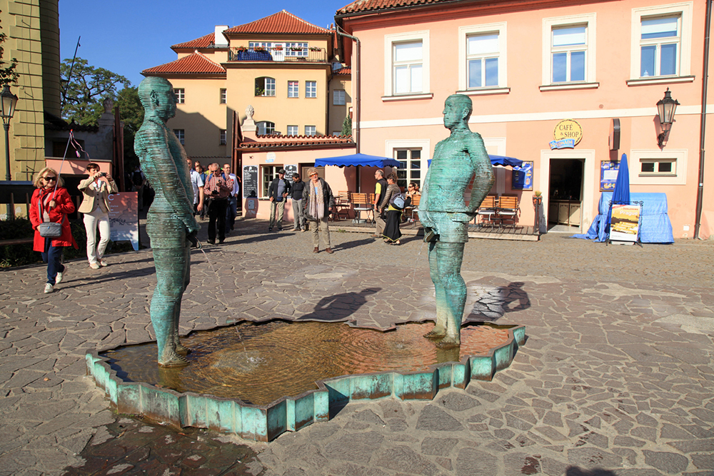 Prague,Czech Republic - October 3, 2015: Tourists and Fountain Pissing Men near Kafka Museum in Prague,Czech Republic. Fountain by David Cerny, sculptor whose works can be seen in many locations in Prague.
