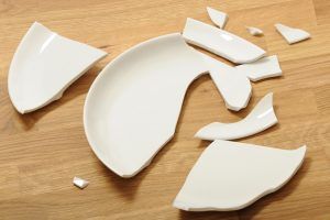 White plate lies broken on the floor.