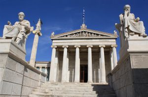 """Neoclassical Academy of Athens in Greece showing main building and statues of ancient Greek philosophers Plato (left), Socrates (right) and goddess Pallas Athena (behind Plato). The Academy of Athens is the highest research establishment in the country and one of the major landmarks of the city."""