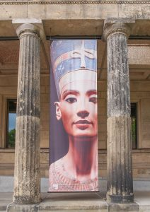 Berlin, Germany - May 10, 2014: Banner of Queen Nefertiti of Egypt (known as Nofretete in German) in front of the Neues Museum which hosts her statue. Thermal anomalies in recent scans of Egyptian pyramids may lead archeologists to find her hidden tomb.