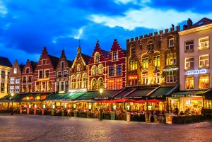 Bruges, Belgium - August 9, 2014: Night image north side of Grote Markt (Markt) with enchanting street cafes, meeting place of the Brugelings and tourists. Brugge, Belgium.