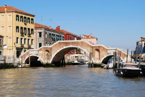Ancient stone bridge with three arches on a canal in Venice, Italy