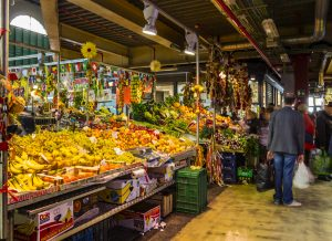 "Florence, Italy - October 29, 2016: Florence, Italy. Fruit and vegetable stall in the City Central Market (""Mercato centrale"" in Italian), and customers with shopping bags."