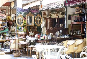 Athens, Greece - September 27, 2013: Monastiraki flea market is located in Monastikari district in down-town Athens. This district has preserved testimonies of the Ottoman era. It features a flea market, many monuments and gorgeous views of the Acropolis Hill. In the photo are some junk shops in which is possible to buy anything. The store owner is visible in the photo shot.