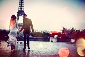 Young couple together in front of an Eiffel Tower in Paris, France - on their first day as married couple.